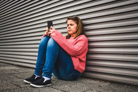 Young woman in jeans and a pink blouse texting on her smartphone – Girl sitting down against a garage door looking serious at her phone