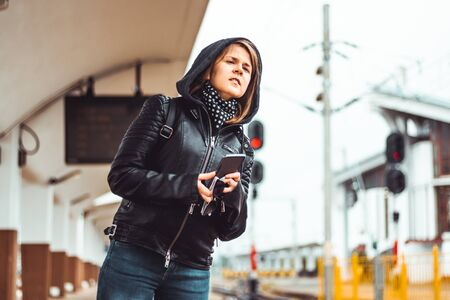 Young woman wearing jeans and a leather jacket holding a smartphone in a station on a rainy day – Pretty girl waiting and looking after the train – Concept image for travel or tourism