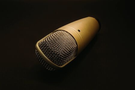 Microphone with yellow metallic body and stainless-steel grid head on a dark background with copy space – Modern music equipment for voice recording – Concept image for freedom of speech