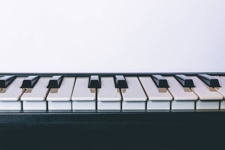 Closeup of white and black piano keys on a white background with copy space – Musical instrument for playing melodies – Concept image for creativity