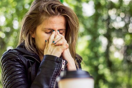 Tired young woman with brown hair bowing her head while holding it with her index fingers in nature – Girl having headache and sinuses pain 스톡 콘텐츠