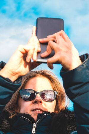 Young woman with brown hair wearing sunglasses with a black smartphone taking a selfie outdoor – Girl holding the phone up and looking at it – Concept image for teens using gadgets