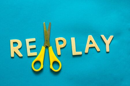 The word replay written from wooden letters and a plastic yellow scissor on a bright blue background