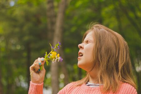 Young woman with brown hair wearing a pink blouse having an allergic reaction to pollen – Hypersensitive girl sneezing while holding a flower bouquet