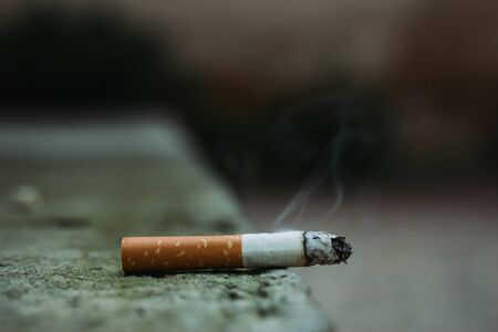 Lit white cigarette with orange filter and smoke coming out of it sitting on the grey city concrete with copy space – Dangerous and toxic habit that causes multiple diseases