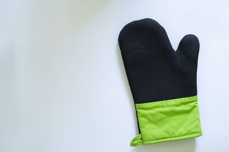 Close-up shot of oven glove with rubber cover for protection against heat and burns – Kitchen mitt made from thick fabric and silicone placed on a white background with copy space