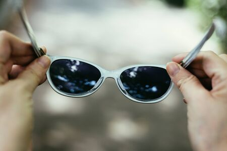 Close-up shot o sf young person holding a pair of stylish black sunglasses outdoor – Woman hand with hipster eye ware on a grey background