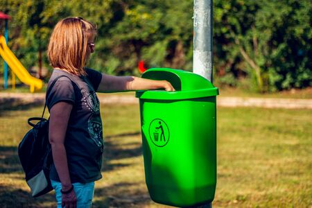 Girl taking care of the environment. People protecting and recycling litter in the park.