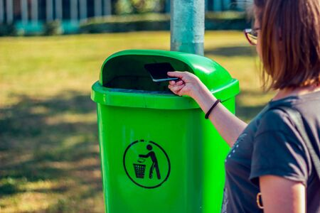 Closeup of a hand throwing a smartphone in a public trash can. Escape from technology and internet concept Stockfoto - 150230681