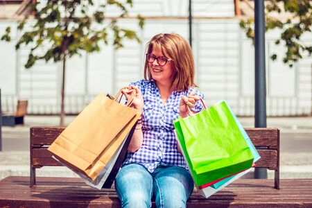 Pretty woman sitting on a wooden bench in an italian city and laughing while she is holding colored paper shopping bags in both hands Foto de archivo