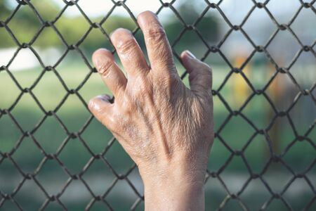 Immigrant hands held on a chain fence – Immigration concept grabbing a metallic mesh at country border Reklamní fotografie