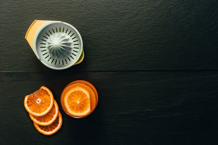 Glass of orange juice top view with fruit slices and a plastic citrus juicer – Fresh summer background with drink on dark black textured stone – Healthy beverage refreshment for diet Stockfoto