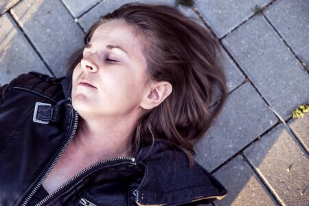 Young woman lying down on ground with eyes closed – Sick or ill girl unconscious outside on concrete sidewalk – Victim of force abuse concept image