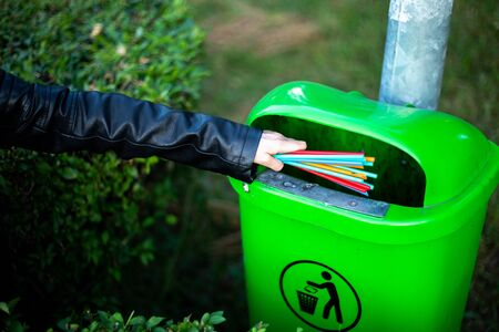 Young person holding multiple straws in front of a green trash can in the park – Girl throwing plastic waste at recycle garbage bin outdoor