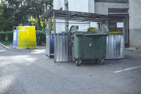 Garbage can area in a residential zone – Urban plastic trash bins of different colors lying next to an apartments block Stockfoto - 150244628