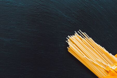 Long yellow spaghetti placed in the bottom right corner on a stone textured table as background - Italian basic food ingredient for different recipes