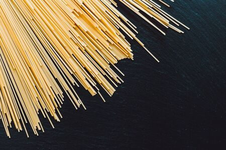 Bunch of long and thin spaghetti placed on the top of a black table as background with copy space - Gluten free pasta on stone textured surface Banque d'images