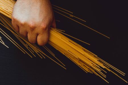 Male hand holding spaghetti on a dark table as background - Person holding long and thin italian pasta over dark stone surfers with copy space Banque d'images