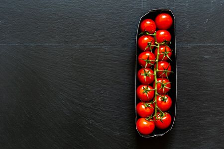 Red cherry tomatoes in a paper try placed vertically on black background with copy space – Natural and organic vegetables full of vitamins and nutrients for a healthy lifestyle
