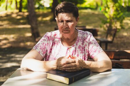 Senior woman praying while reading from the Bible - Beautiful old lady holding her hands on top of the Holy Book while thinking in the park - Religious person feeling spiritual in nature
