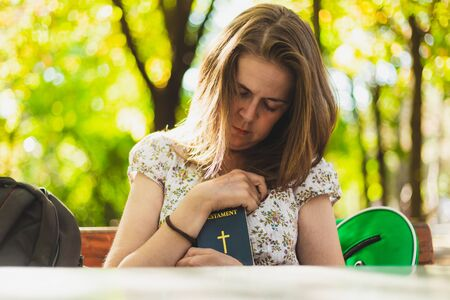 Young woman holding small Bible next to her heart while standing on a bench in the park - Pretty girl with brown hair praying with the Holy Book at her chest Foto de archivo