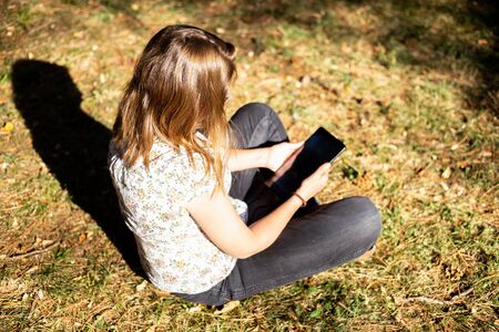 Young woman using a tablet on a sunny day while standing on the grass - Pretty girl with brown hair holding mobile gadget in the park