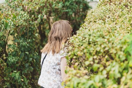 Scared young woman hiding in fear behind a bush outdoors - Rear view of anxious cute girl sitting in the park and looking for threats
