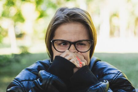 Portrait of a young woman feeling cold outdoors - Pretty girl with brown hair wearing leather jacket and eyeglasses trembling in the park - Female trying to warm up in nature 版權商用圖片