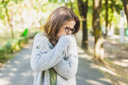 Young woman trembling and feeling cold outdoors - Thick dressed girl with grey jumper wearing eyeglasses freezing while walking in the park in autumn