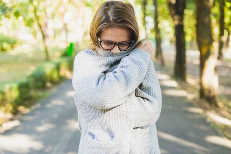 Young woman holding her hand around her while feeling cold outdoors - Pretty girl wearing eyeglasses and thick clothes trembling in the park - Female freezing in nature while trying to warm up her arms
