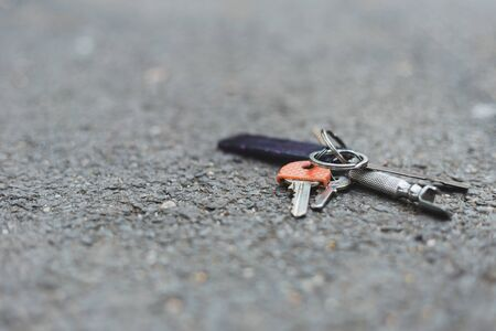 Close-up shot of lost keys on the ground on a sidewalk with copy space - Metallic home accessory used for opening the looks and entrance doors placed on a rough surface outdoors