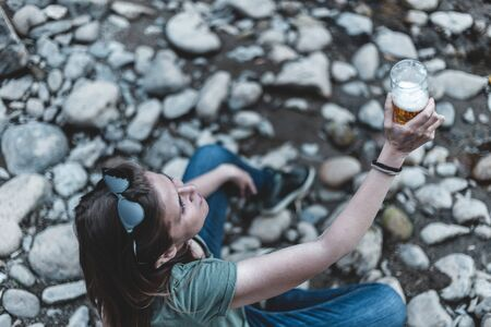 Young woman holding a glass of fresh beer while standing near a river - Pretty girl cheering with a pint of cold beverage in nature - Happy casually dressed female rising mug of alcoholic drink
