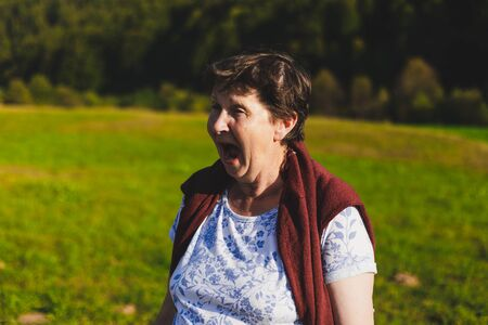 Senior woman yelling with wide opened mouth outdoors on a sunny day - Angry old lady screaming in nature - Cute elderly person having a moment of rage while walking in the park