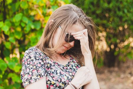 Smiling shy young woman looking down while holding one hand to her forehead outdoors - Cute girl with brown hair wearing sunglasses feeling embarrassed and trying to cover her face in the park Stock fotó
