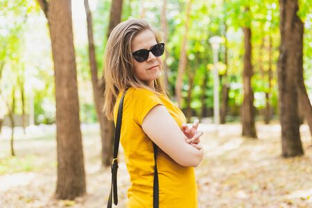 Impatient and angry young woman standing outdoors with crossed hands - Casually dressed girl wearing sunglasses waiting for someone that is late Archivio Fotografico
