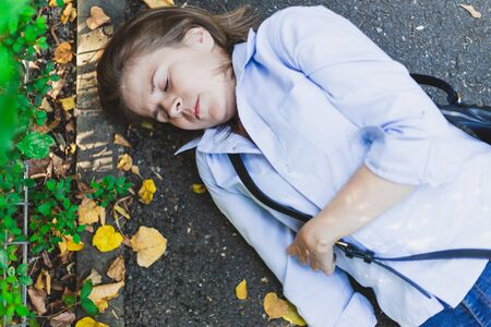 Lying fainted sick woman with heart problems outdoors - Epileptic woman fallen on the ground after seizure caused by stress - injured young female on the street after accident