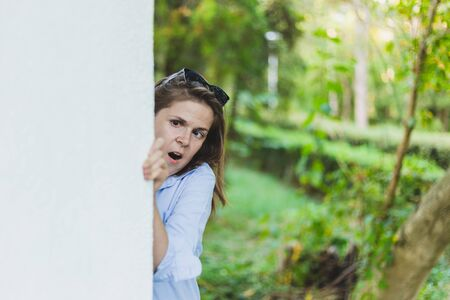 Scared young woman hiding behind a wall outdoors - Fearful cute girl with brown hair finding shelter after a building on a summer day - Panicked and anxious female in the city Foto de archivo