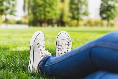 Person wearing sneakers and jeans while sitting on the grass in the park - Trendy dressed millennial girl with white canvas shoes and denim pants relaxing outdoors - Fashionable summer outfit
