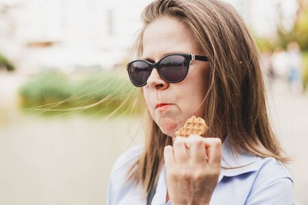 Young woman holding a healthy cereal biscuit while taking a bite from it - Pretty girl eating a sweet and nutritious desert made out of whole grains - Concept image for healthy breakfast