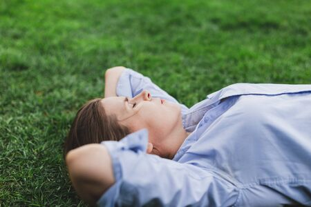 Tired young woman sleeping outdoors while lying in the grass - Cute female worker drained by energy taking a nap in nature - Girl with brown hair holding both hands under her head relaxing with eyes closed in the park Фото со стока
