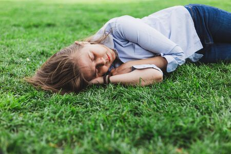 Tired young woman sleeping outdoors on the grass - Stressed female worker taking a nap in nature holding head on her hands - Beautiful girl with brown hair wearing blue shirt relaxing on a green lawn