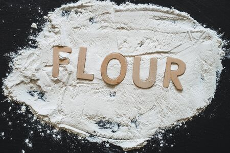 White wheat flour with the word flour written in it with wooden letters on a dark stone slate as background - Basic and common ingredient used in bakery and pastry