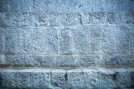 Grey rough textured brick wall - Architectural background of cracked and weathered building exterior - Solid stone structure with grungy surface Archivio Fotografico