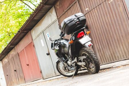 Motorcycle with small plastic carrier parked in front of garages with copy space - Small and fast mean of transport in the city or trips - Handy and easy to control vehicle Stock fotó