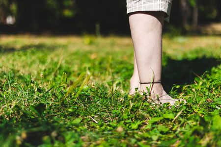 Young person standing with feet in the grass on a sunny day - Girl wearing brown bracelet on her ankle relaxing barefoot in the park - Enjoying simple way of leisure on a fresh green meadow Stock fotó