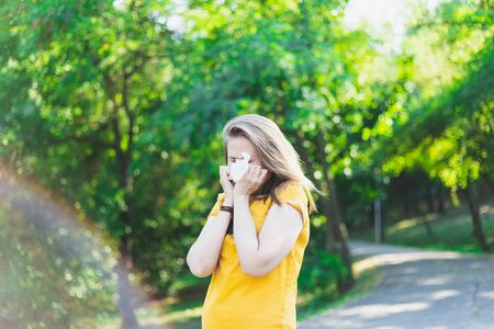 Girl having an pollen allergy in nature - Woman using handkerchief outdoors while sneezing - Teenager cleaning her nose with a paper tissue 版權商用圖片