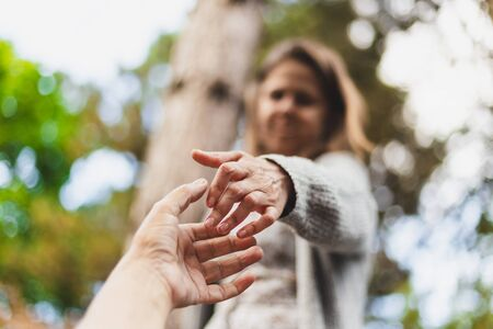 Woman with arthritis reaching out for help outdoors on a sunny day - Golding a hand of an injured person with physical disability in the park - Concept image for helping others