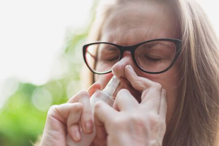Woman using nose spray for allergies outdoors - Portrait of cute girl wearing eyeglasses administering nasal treatment for seasonal allergies - Saline medicine for respiratory problems 版權商用圖片