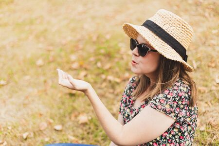 Smiling woman blowing air kiss while walking in nature - Casually dressed female with summer hat and sunglasses sharing love on a beautiful natural background Stock fotó