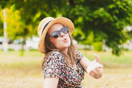 Happy beautiful young woman sending air kiss outdoors - Attractive millennial girl wearing summer hat and sunglasses sharing love in the park on a sunny day - Pretty female blowing kiss in nature Stock fotó - 150296745